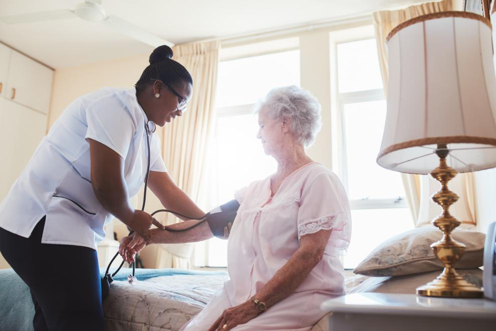 Nurse assists older woman in home